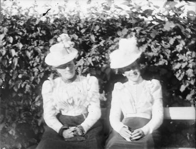 To kvinner i lyse bluser og mørke skjørt sitter på en benk med en hekk i bakgrunnen