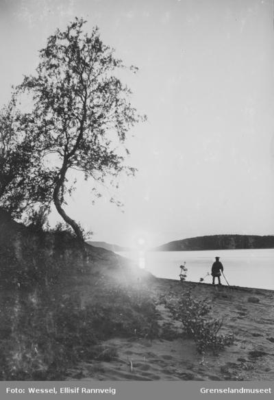 En mann i siluett står og ser utover Soldatbukta i midnattsol