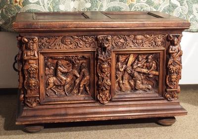 Kiste som har forside med bibelske motiver i to fyllinger flankert av karyatider