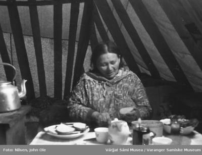 En kvinne sitter i lavvoen og smører brødskiver