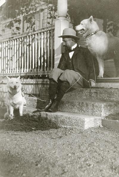 Albert Petersson saman med to hundar på trappa til disponentvillaen i Alby