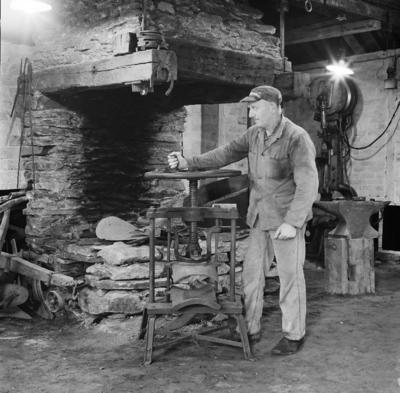Olav Mæland demonstrerer en gammel skruepresse i bedriftsmuseet til Kvernelands Fabrikk AS