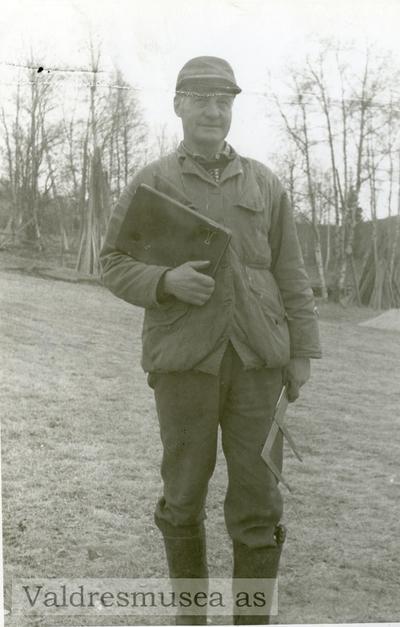 Mann med notatbok og måleutstyr foran noen trær