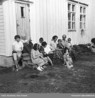 En del folk sitter foran en bolig i Neiden
