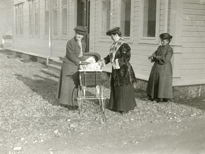 Tre vinterkledde kvinner og baby i barnevogn framfor kontorbygget til cyanamidfabrikken i Odda