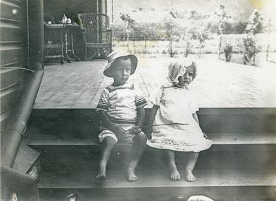 Klaus Petersson og ei ukjend lita jente i sommarklede på terrassen utanfor Peterssons villa