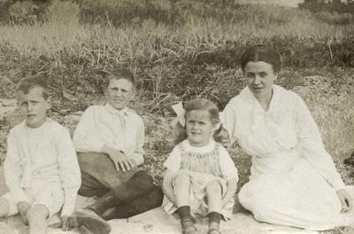 Ung kvinne og tre barn sitjande på grasbakke