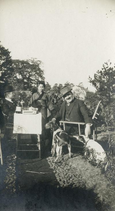 To menn og ei kvinne i kimono rundt eit hagebord med stor vinflaske og oppdekking