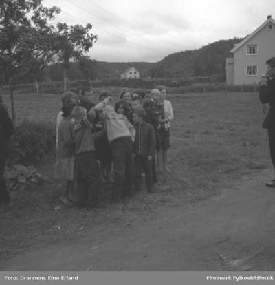 Noen barn og ungdommer står i en klynge ved en grusvei i Neiden