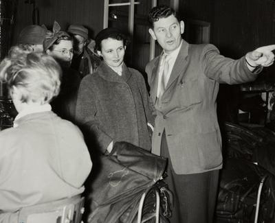 Avdelingssjef i Konfeksjonsfabrikken Knutsen viser en gruppe kvinner rundt i konfeksjonsfabrikkenes lokaler