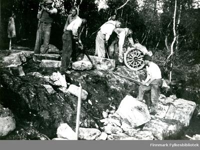 Bildet viser 7 personer i arbeid med muring av stikkrenne