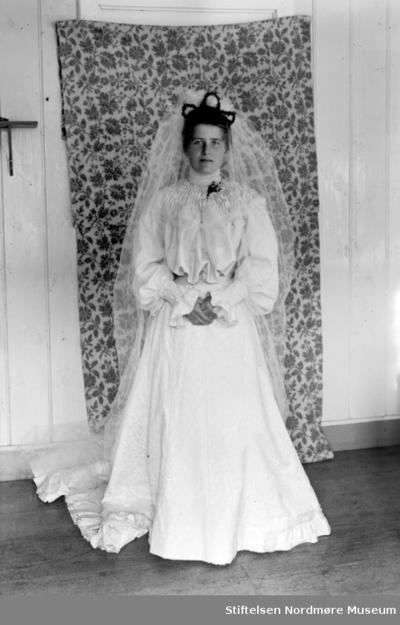 Brudeportrett av en kvinne iført brudekjole og slør