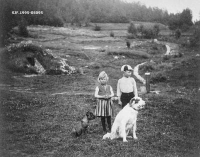 To barn og to hunder ved vannpost