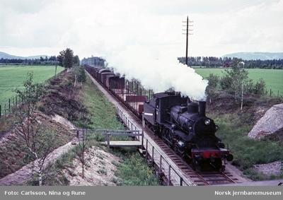 Damplok type 27a med nordgående godstog passerer Vangerud holdeplass