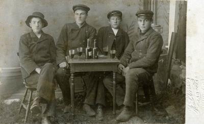 Fire menn med flasker og glass fotografert i telt på Liland