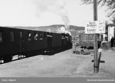 Larvik stasjon med smalsporet tog i spor 1 og skilting