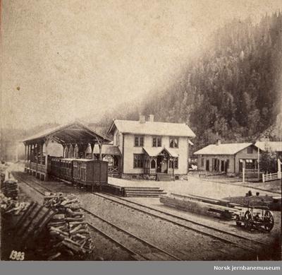 Støren stasjon med stasjonsbygningen og den overbygde plattformen - persontog på stasjonen