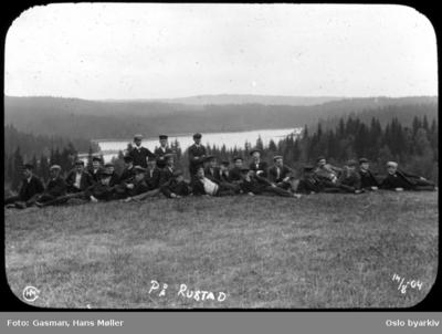 En gruppe menn hviler på gressbakken