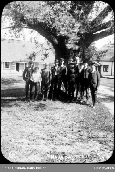 En gruppe menn poserer foran en stor eik (?) på Hakadal verk