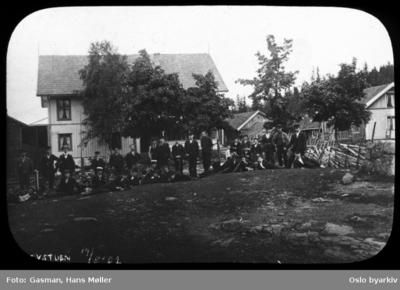 En gruppe menn og ungdommer i penklær poserer for fotografen ved Kleivstua