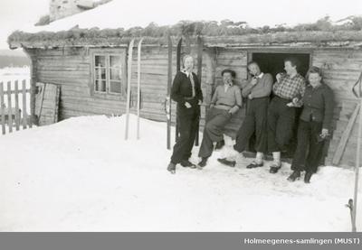 Tre kvinner og to menn utenfor en hytte