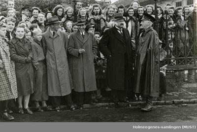Menn i hatt og frakk med tilskuere bak seg