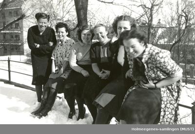 Seks kvinner sitter på et gjerde