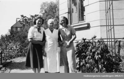 Tre kvinner utenfor en murbygning (antatt studentbolig