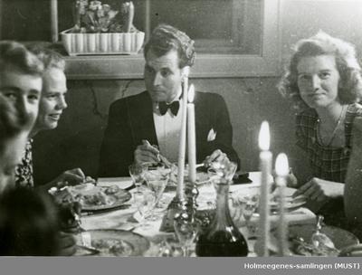 To kvinner og en mann ved et middagsbord dekket til fest