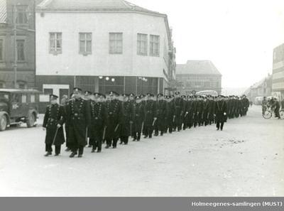 Politifolk marsjerer på rekke og rad gjennom en gate