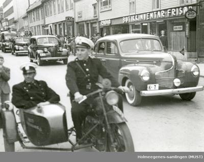 Politifolk kjørende på motorsykler med sidevogn og i biler