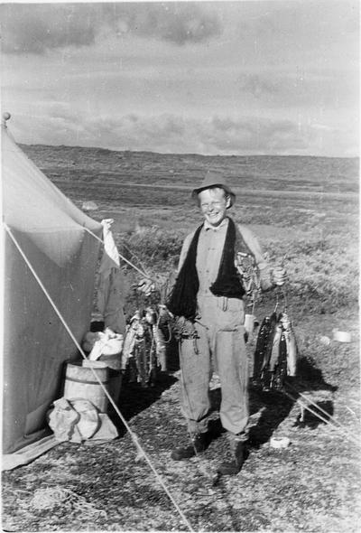 Fra foredragsrekken Landmålerlivet i Finnmark v/Axel Printz : Assistent Per Oppi med fiskefangst