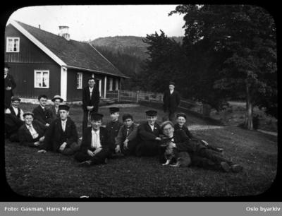 En gruppe menn og ungdommer poserer for fotografen på gressbakken foran hovedhuset