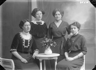 Enligt senare noteringar: Ateljéfoto av fyra damer, klädda i fina klänningar.