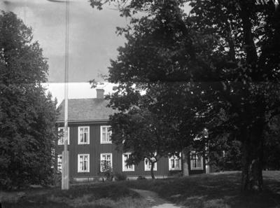 Enligt tidigare noteringar: Tvåvånings bostadshus i trä, i trädgården flaggstång. (gul slöja på plåten).