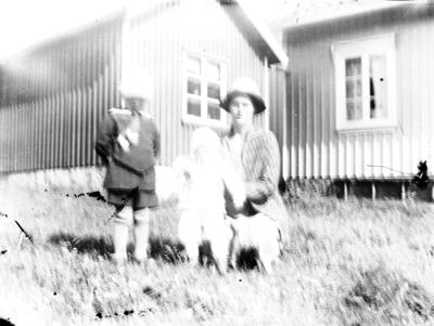 Troligen mor med barn framför boningshuset.