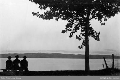 Tre män sitter på en bänk och ser ut över Vätterns vatten med Huskvarna till höger i bakgrunden.