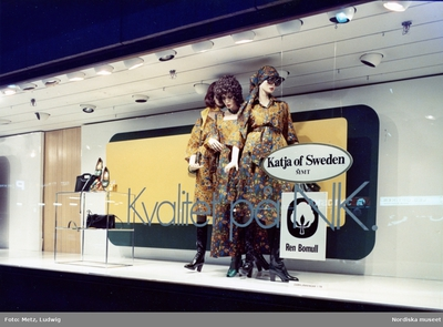8aecb726d6e Skyltfönster på Nordiska Kompaniet. Skyltdockor i kläder från Katja of  Sweden. Klänning, blus och sjal i samma mönster. Accessoarer på ett bord.