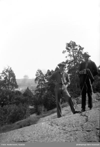Fotograf Gustav Andersson med sin kamera tillsammans med en annan man på berget i Jönköpings stadspark.