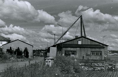 Oskarshamns varv. Förrådsbyggnad av plåt vid haveristkajen. bakom skjulen stora saxkranen.