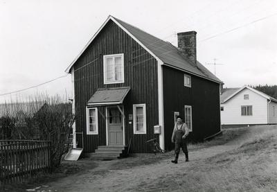 Ångermanland, Trysunda. F.d. fiskaren Karl Fritjof Lindkvists stuga, tillika Trysundas postkontor, öppet en timme per dag. Det är fiskaren Ola Lundgren som är på väg förbi.
