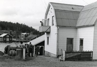 Ångermanland, Trysunda. Folk samlas utanför Konsum och väntar på Nätra Express ankomst. På balkongen Anna Greta Lundström, som sköter affären.