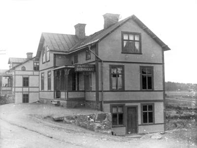 Fannagatan 37 närmast (Södra området 3C), Enköping, sett från norr. På huset sitter en skylt med texten J. A. Johansson, Skomakare.