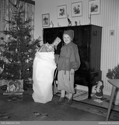 Det är jul hemma hos familjen Andersson i Huskvarna och Tom står bredvid julklappssäcken.