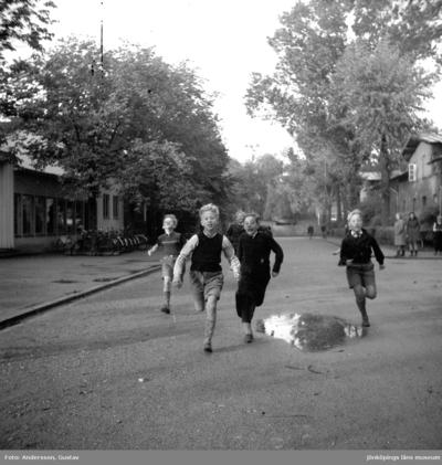 Några pojkar har kapplöpning på Kvarngatan i Jönköping, nuvarande Lagermansgatan. Till vänster syns idrottshuset och den numera rivna tennishallen.