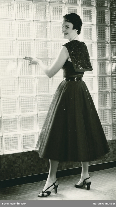f3d6c622ef3a EM, Modellbutiken, Nordiska Kompaniet, Damkonfektion. Modell i klänning med  utställd kjol,