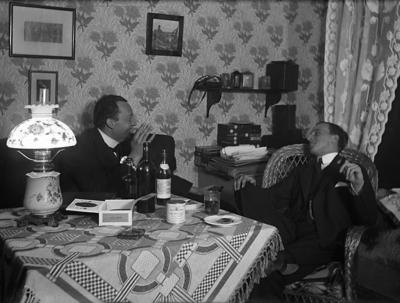 Två män sitter i samspråk vid ett välfyllt bord.  I bakgrunden syns bl a en hylla med några askar för glasplåtar m.m. och en kamera.   Mannen till höger Ragnar Ahnström 1894-1936 Fotograf. Källa: Stig Christoffersson.  Jämför med UMFA53247:0698.