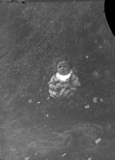 Ett barn som sitter på gräsmattan.  Glasplåten trasig.