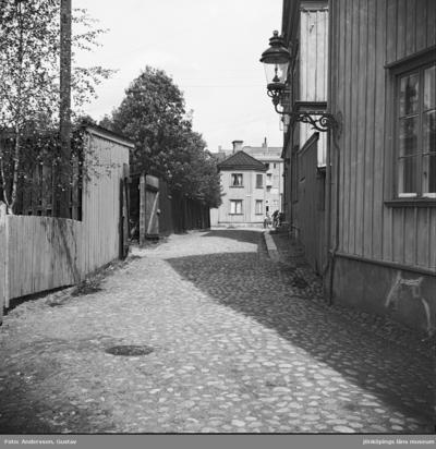 Kullerstensgata i Jönköping. Till vänster plank och mitt emot trähusfasader med en väggfast gatlykta.