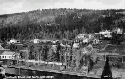 Vy över Stadsbacken och Norra Stadsberget i förgrunden Selångersån, till höger idrottsplatsen och hopptornet och på berget utsiktstorn. Text till bild